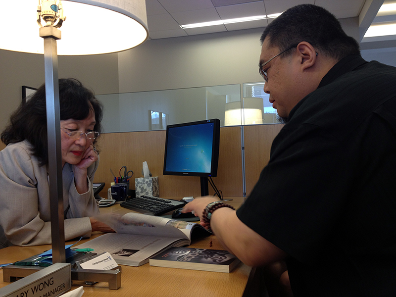 Rinpoche explains his books to a nice lady at the bank