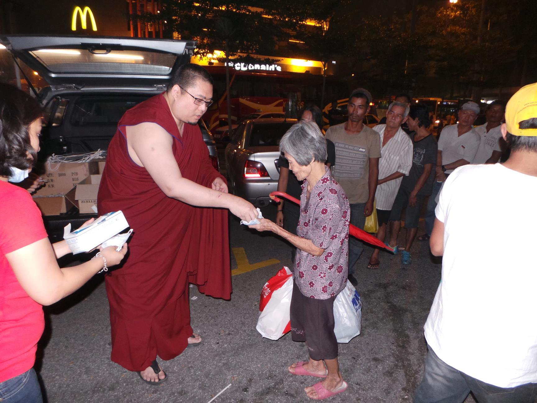 Rinpoche distributing face masks and eye drops to the homeless during a particular bad haze in Kuala Lumpur