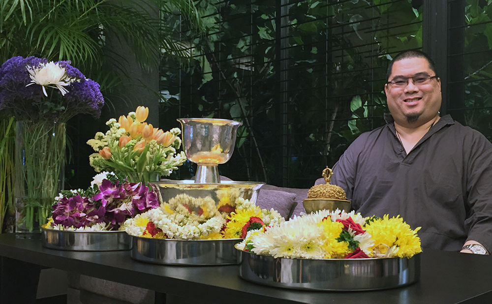 Tsem Rinpoche with flowers about to be offered up to Vajra Yogini and Dorje Shugden